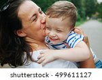 Small photo of Happy family, friends forever concept. Smiling mother and little son playing together in a park. Mum holding shy baby. Sunny windy summer day. Outdoor shot