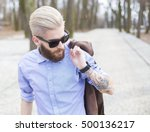 Blond hipster guy in shirt with tatoo on arms representing youth culture.