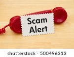 Small photo of Getting a call that is an scam, A retro red phone with note card on a desk with text Scam Alert
