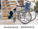 Small photo of Empty wheelchair and stairs. Disabled accessibility reality.