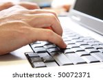 A pair of hands typing into a laptop computer. - stock photo