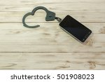 Small photo of Phone connected to handcuffs fetters. concept of addiction dependence