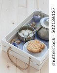 Small photo of Maple leaf shaped cookie, sugar cubes and a pewter teapot on a white wooden tray. Copy space