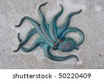 Bronze octopus on concrete background - stock photo