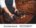 Worker Polishing A Pair Of Shoes