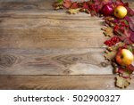 Small photo of Border of apples, acorns, red berries and fall leaves on the old wooden background. Thanksgiving background with seasonal berries and fruits. Abundant harvest concept.