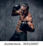 Small photo of Aggressive shirtless boxer on grey background.