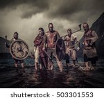 Small photo of A group of armed Vikings, standing on river shore.