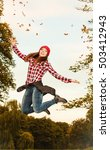 Small photo of Happiness carefree. Woman relaxing in autumn park jumping throwing leaves up in the air with arms raised up outdoor.