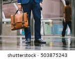 Small photo of Closeup Of A Businessman Holding leather Briefcase Going To Work after rain