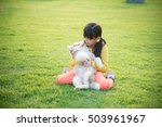 Stock photo beautiful asian girl playing with siberian husky puppy in the park 503961967