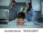 Small photo of Upset boy sitting while couple having argument in background at kitchen