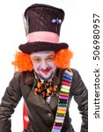 Small photo of The insane funny Hatter: a man dressed in a velour brown frock coat, cylinder hat and the bow tie grimacing and is playing the fool - close-up portrait, isolated