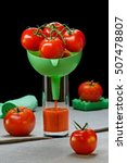 Small photo of Tomatoes in a funnel in glass with tomato juice