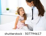 Small photo of Doctor examining a little girl by stethoscope. Medicine and health care concept.