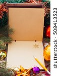 Small photo of Empty sketchbook with golden snowflake, xmas frame. Brown paper notebook with pencil and Christmas tree branches and trumpery, free space for text or greeting
