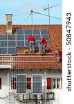 three worker installing solar panels on roof - stock photo
