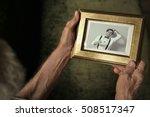 elderly man holding photo frame ...