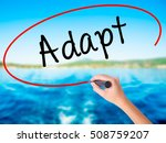 Small photo of Woman Hand Writing Adapt on blank transparent board with a marker isolated over water background. Business concept. Stock Photo