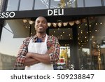 Small photo of Black male business owner standing outside coffee shop