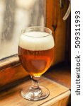 Small photo of Regular class of amber ale on a wood windowsill