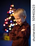 Small photo of Kid and multicolor spruce with decorations and lights bokeh. Child and gifts under the multicolour Christmas tree. Little boy and adornment on the trees