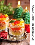 "Small photo of Traditional New Year's Russian salad ""Mimosa"" with salmon, potatoes, cheese, carrots and eggs."