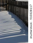 Small photo of fence shadow on snow accumulated deck