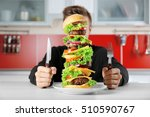 man eating huge burger at table | Shutterstock . vector #510590767