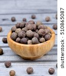 Small photo of Bowl with allspice on grey wooden table