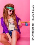 Small photo of Pretty girl with dreadlocks and green do-rag sitting near the rose skateboard