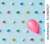 Small photo of Pink baloon with colorful pins on blue background. Adversity or unique concept. Flat lay. Top view.