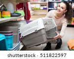 Stock photo smiling young female customer buying kennel for pet in shop 511822597