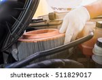Small photo of auto mechanic wearing protective work gloves holding a dirty, air filter over a car engine for cleaning