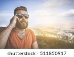 Small photo of Summer sunny day. Front view of young bearded man in sunglasses and brown T-shirt standing and talking on mobile phone. In background mountain landscape with bird's-eye view. Man uses digital gadget.