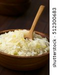 Small photo of Sauerkraut in wooden bowl, photographed with natural light (Selective Focus, Focus one third into the sauerkraut)