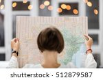 Small photo of Young beautiful female traveler standing on the street with window and light. Trendy look searching direction on location map while traveling abroad.