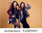 Small photo of Two seductive young women, fashionable girls posing indoor. Amazing windy hairstyle, bright make up, casual winter outfit. Expression.
