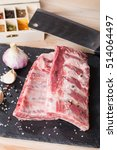 Small photo of Fresh pork ribs, meat marinated and prepared for roast with garlic allspice on wooden background
