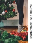 Small photo of Woman decorating a christmas tree and standing tiptoe