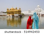Small photo of Two Indian women wearing beautiful and colorful sari dress stand staring in admiration of the Golden Temple, Amritsar, Northern India