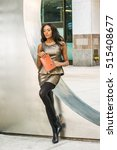 Small photo of I love reading book. African American woman wearing metal crystal sleeveless mini dress top, skit suit, black leggings, high heels, holding red book, leans against silver metal wall, sad, thinking.