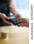 Small photo of Man paying bill through payment terminal in cafe
