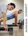 Small photo of Portrait of two men doing aerobic exercise on stepper in fitness studio