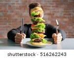 Man Eating Huge Burger At Table