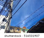 Small photo of Old buildings and busy cable pole in small allay