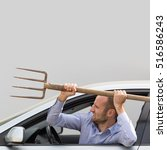 Small photo of Aggressive and violent driver armed with a pitchfork. Copy space on the gray background.