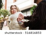 Small photo of Boring man accosting to woman at crowded street