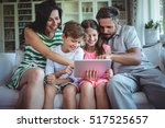 parents sitting on sofa with... | Shutterstock . vector #517525657