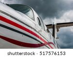 Small photo of Detail of the paint job on Piper PA-42 Cheyenne IIIA under heavy dark clouds. View from abeam the nosegear to the rear with the typical T-Tail in the background.